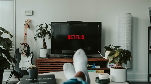 Someone's feet on a table and a TV ahead showing the Netflix loading screen