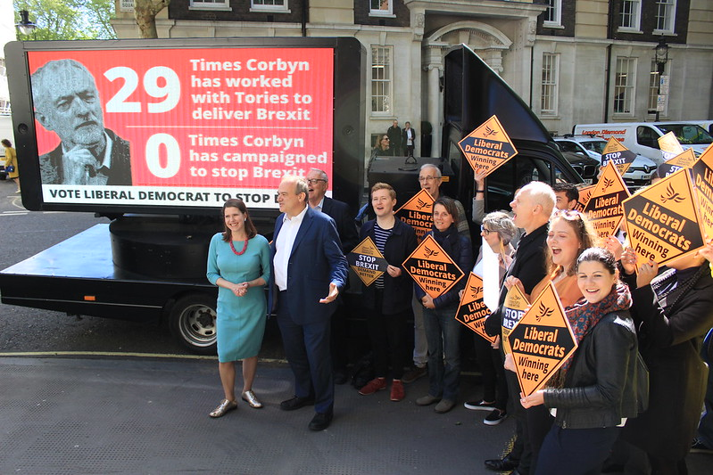 A photograph of the Leader and Deputy Leader of Liberal Democrats, along with party campaigners, canvassing outdoors.