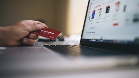 Someone holding a red credit card looking at a computer monitor with an online shopping site